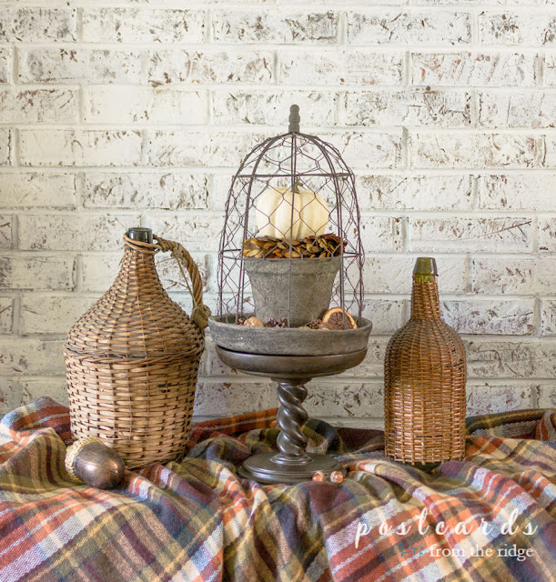 fall decor with wicker demijohn and pedestal with chicken wire cloche