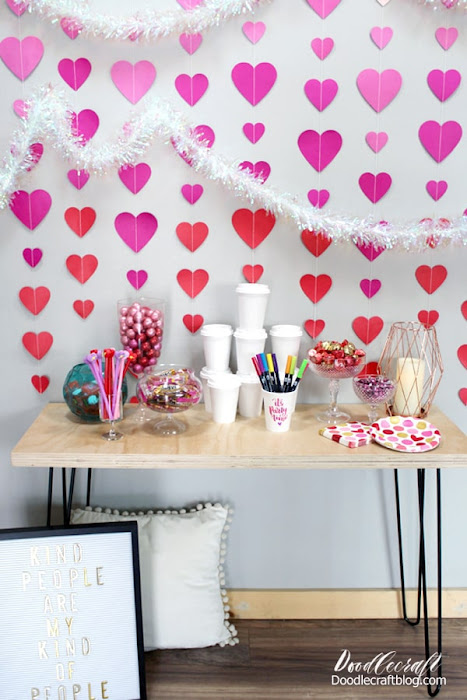 Use a hairpin leg table, a letterboard with a cute saying, some candy dishes, an ombre heart backdrop and some paper coffee cups to decorate for the perfect Galentine's day party.