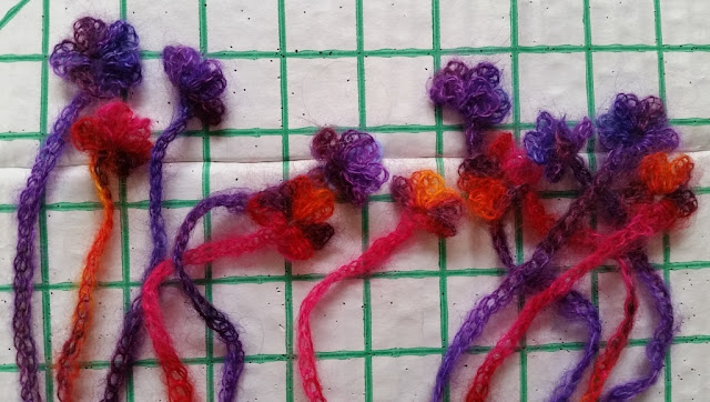Silk mohair fringes made of chains with floral motifs at the end of each chain. Colours include purple, orange and pink.