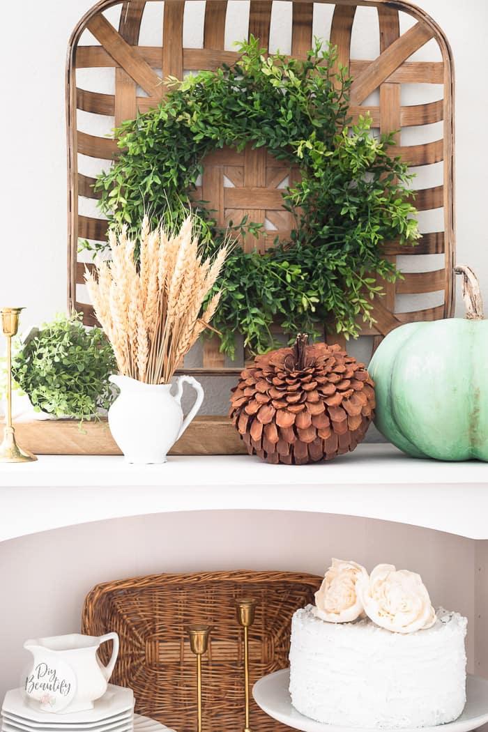pinecone pumpkin, heirloom pumpkin, bundle of wheat on white bookcase
