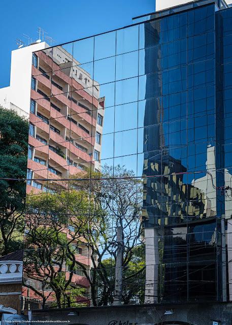 Reflexos em um edifício com fachada de vidro na Carlos de Carvalho