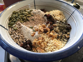 Bowl with dry flours, dried fruit, nut and seed for bread by Corina Duyn