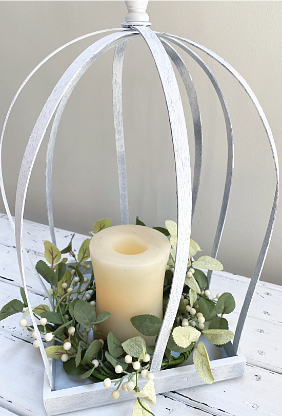 white lantern with wreath and candle
