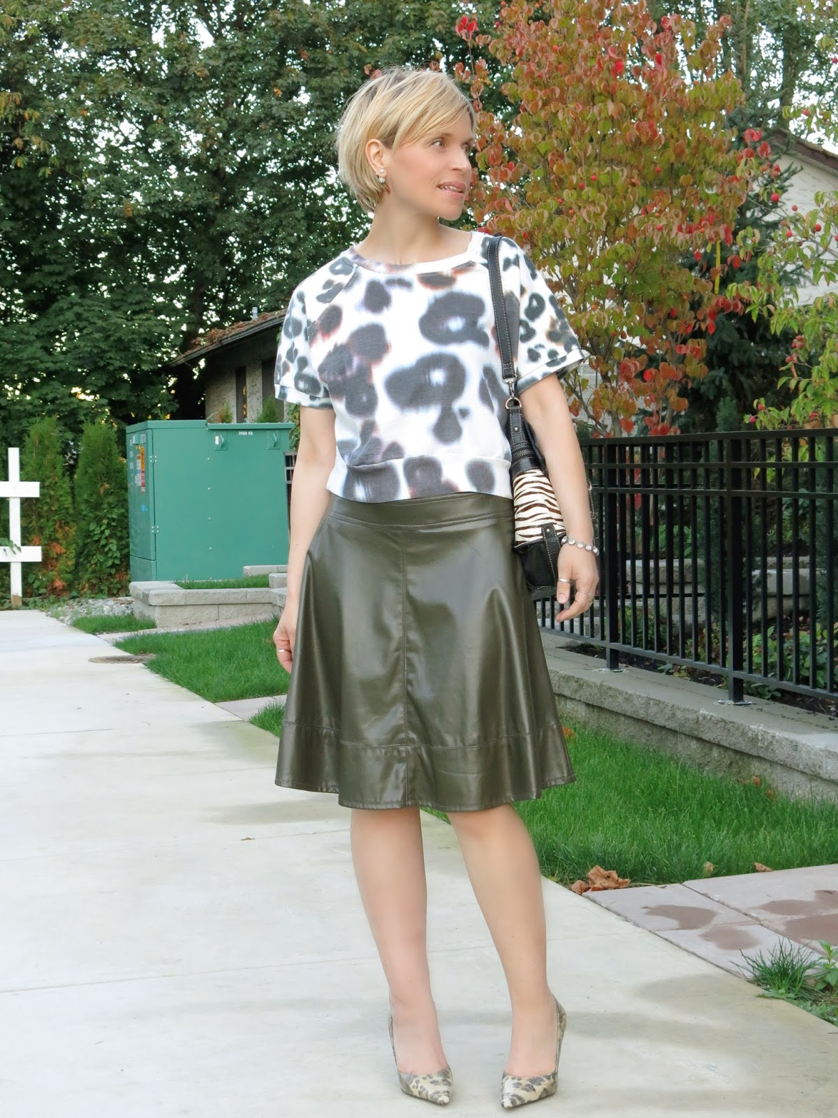 styling a cropped patterned sweatshirt with a pleather skater skirt and animal-print pumps