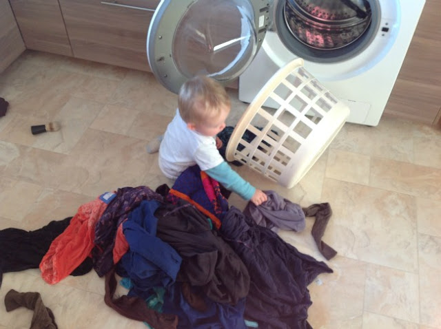 child putting wet washing out of basket onto floor