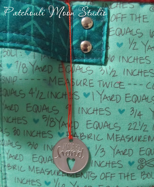 """closeup of metal tag hanging from fabric container that says """"made by hand"""" and depicts a cut out heart"""