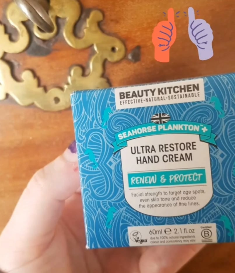 Beauty Kitchen hand cream held up in front of antique wood