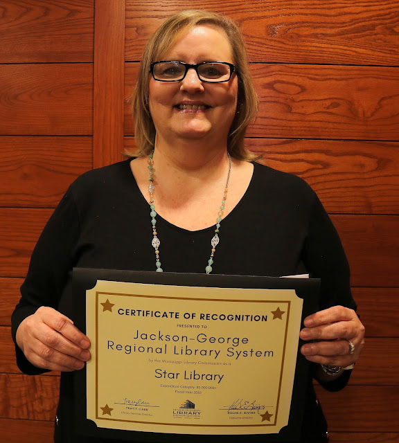 smiling woman holds a certificate of recognition for jackson george regional library system