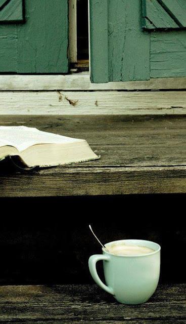 Libro con un café en una escalinata de madera