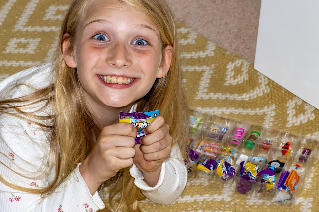 An excited looking 9 year old girl feeling a small sealed plastic bag