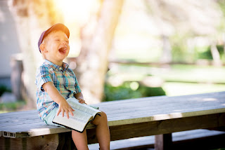 God is inviting us to enjoy Him - boy laughing reading bible