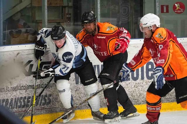 Hokejisti cīnās par ripu pie laukuma borta