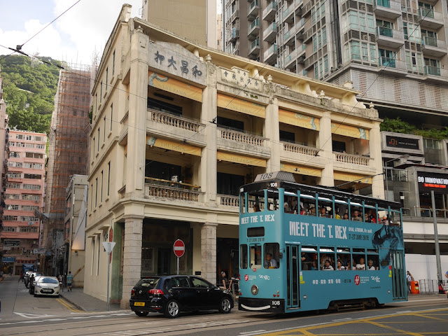 "Hong Kong tram with a ""Meet The T. Rex"" ad going by The Pawn in Wan Chai, Hong Kong"