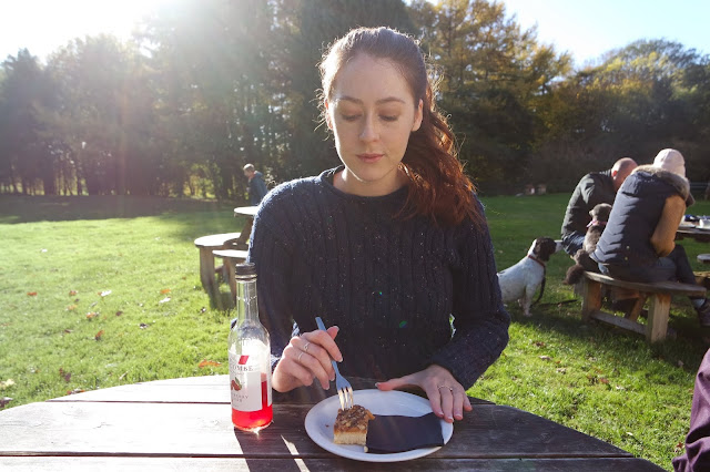 I'm sitting at a sunny table outdoors wearing a dark blue jumper and eating a piece of cake