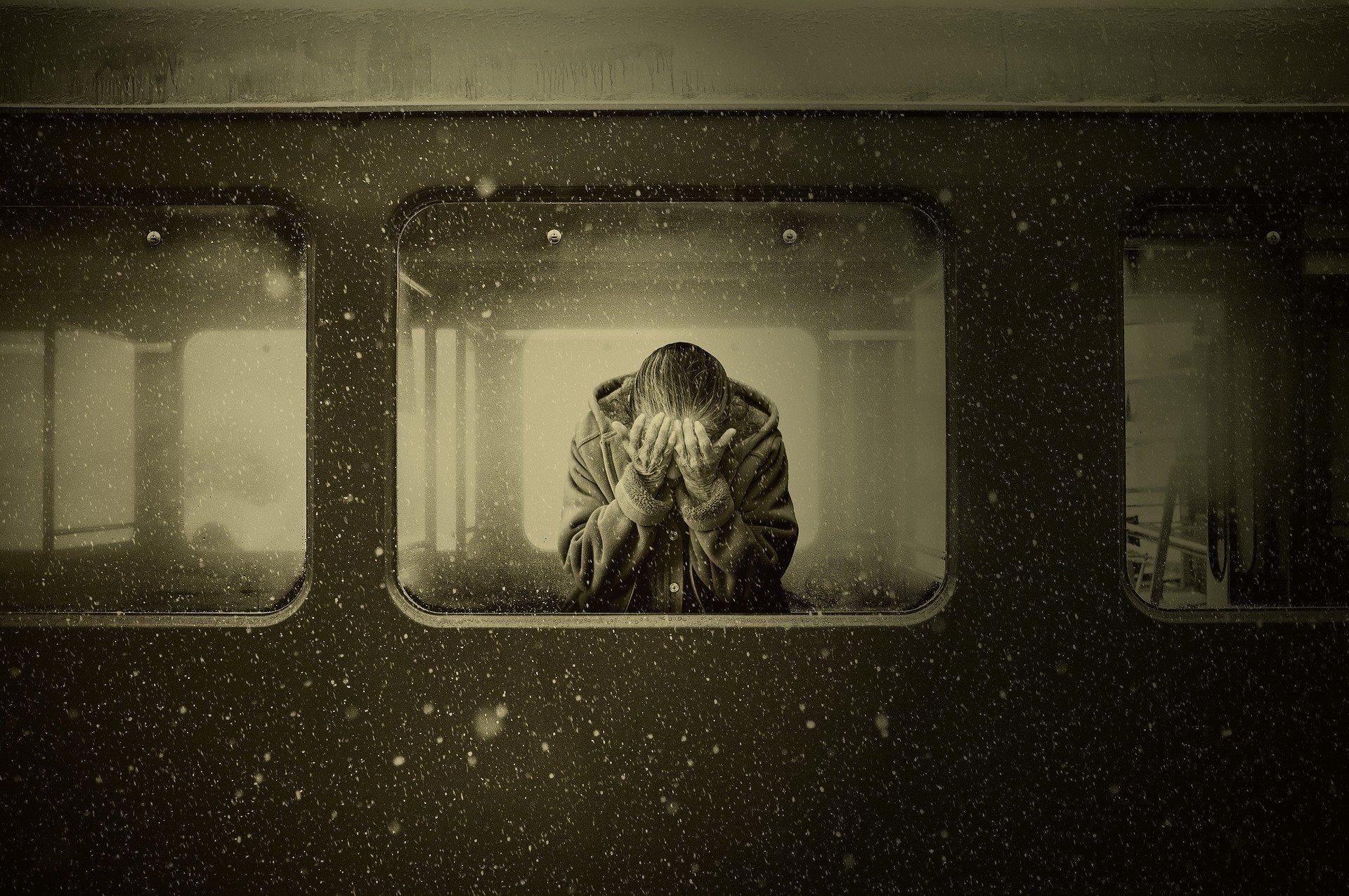 صورة لشخص يقف على نافذة القطار وهو يضع يديه على عينيه
