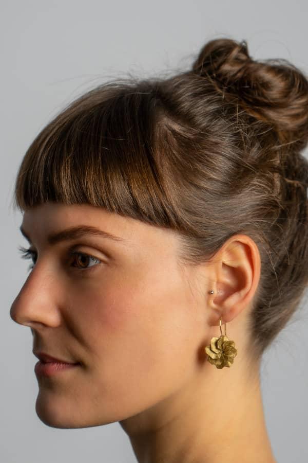 circular golden folded paper origami earring on model
