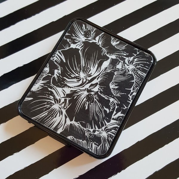 MAC eyeshadow palette with hologram black and white floral lid sitting on striped backdrop