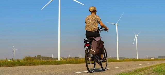 Una mujer pasa en bicicleta junto a unos turbinas eólicas en una carretera rural de Heijningen (Países Bajos).   Unsplash/Les Corpographes