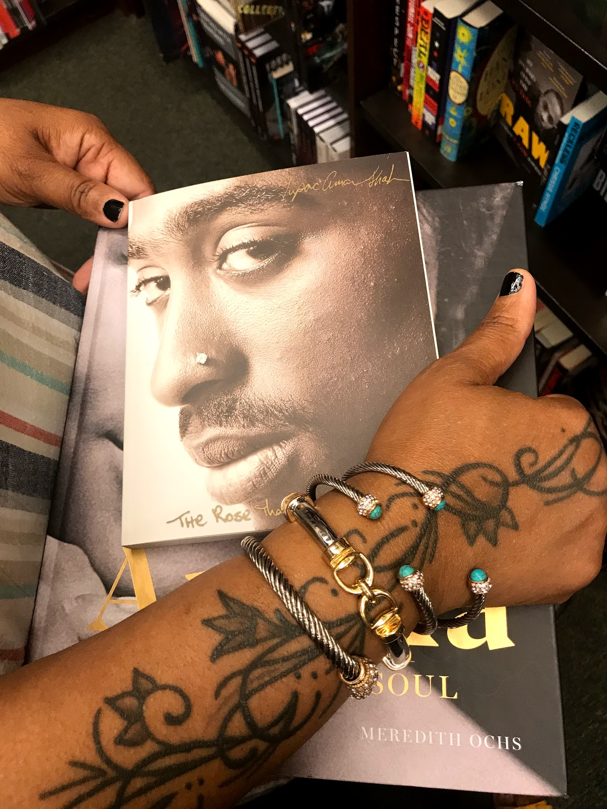 Image: Woman holding books with Tupac face on it at the library. Seen first on Bits and Babbles Blog
