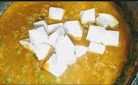 Cooking matar paneer gravy with paneer