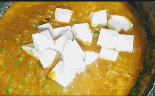 Cooking matar paneer gravy with paneer