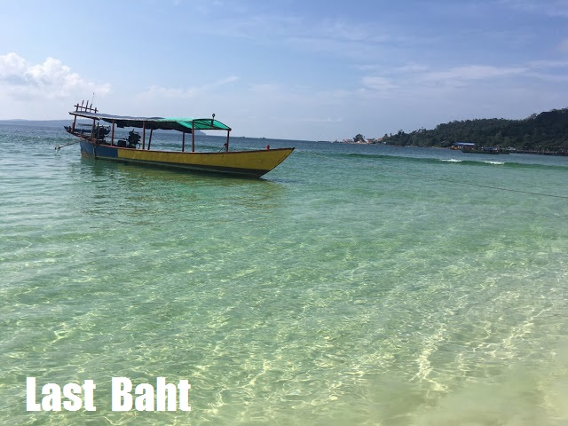 a yellow boat floating on the clear blue waters of Koh Rong Island, Cambodia