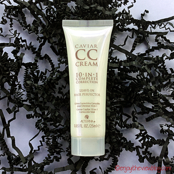 Alterna Caviar CC Cream 10-in-1 Hair Protector sample tube lying on crinkled black paper strips on a white table