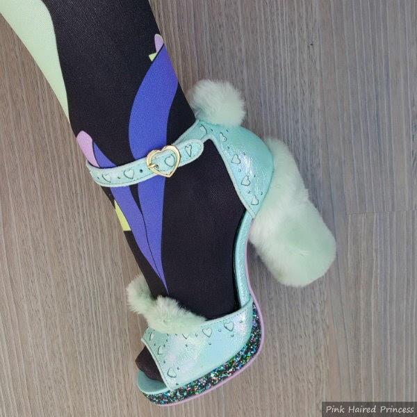 close up of foot wearing mint green glitter and furry shoes with black Maleficent print tights
