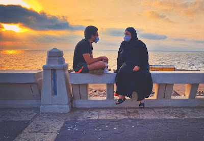 A mother and a son wearing face masks in Alexandria by Mina Moufeed