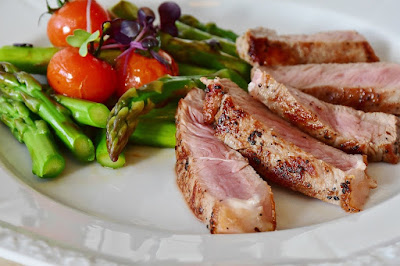 Veal stakes with asparagus and tomatoes.