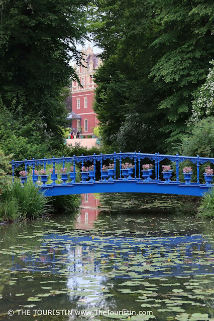 Yellow water lilies in front of a bright- to dark blue iron bridge under large trees with a red painted castle in the distance.