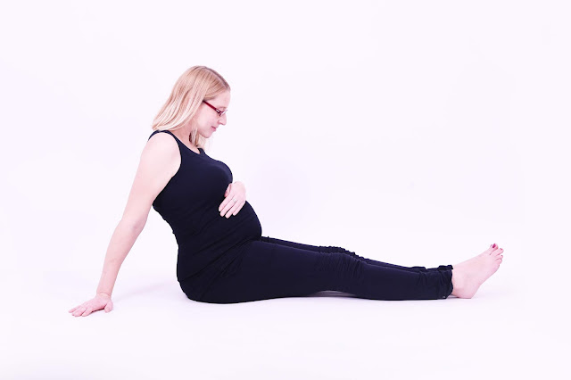 Maternity photo shoot picture at 37 weeks pregnant sitting on the floor in black