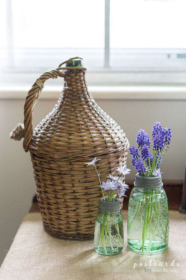 little mason jar vases with flowers and a vintage wicker demijohn
