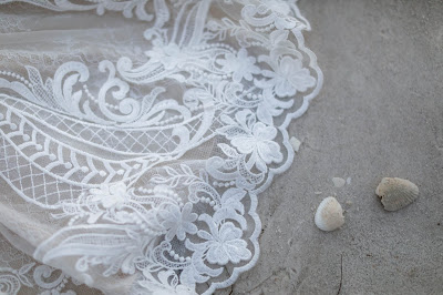 wedding dress in the sand with shells