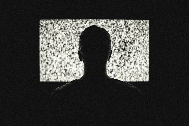 Person watching static on a tv