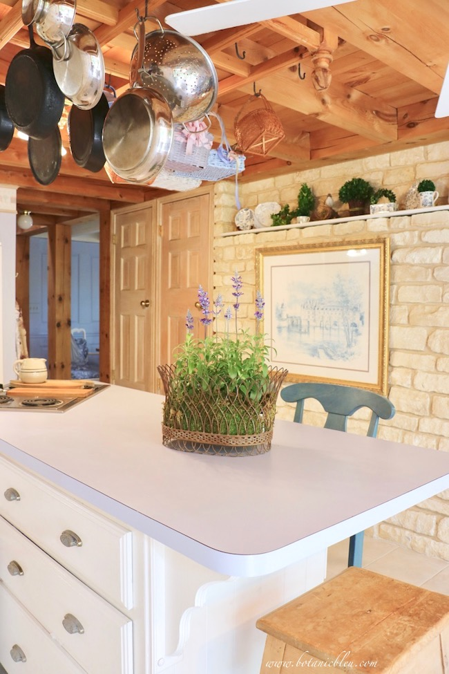 budget wise blue laminate countertop in French inspired post and beam house with limestone wall