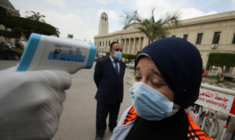 A woman tested for high temperature at Cairo university in April
