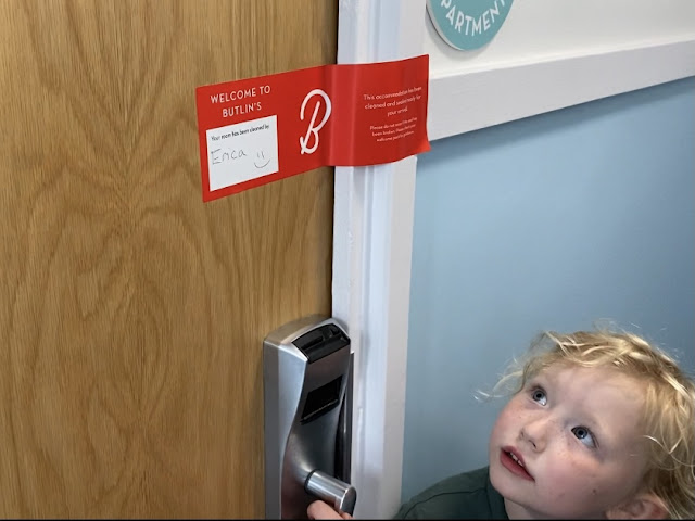 A child looking at an apartment door at Butlin's showing it is sealed before entry