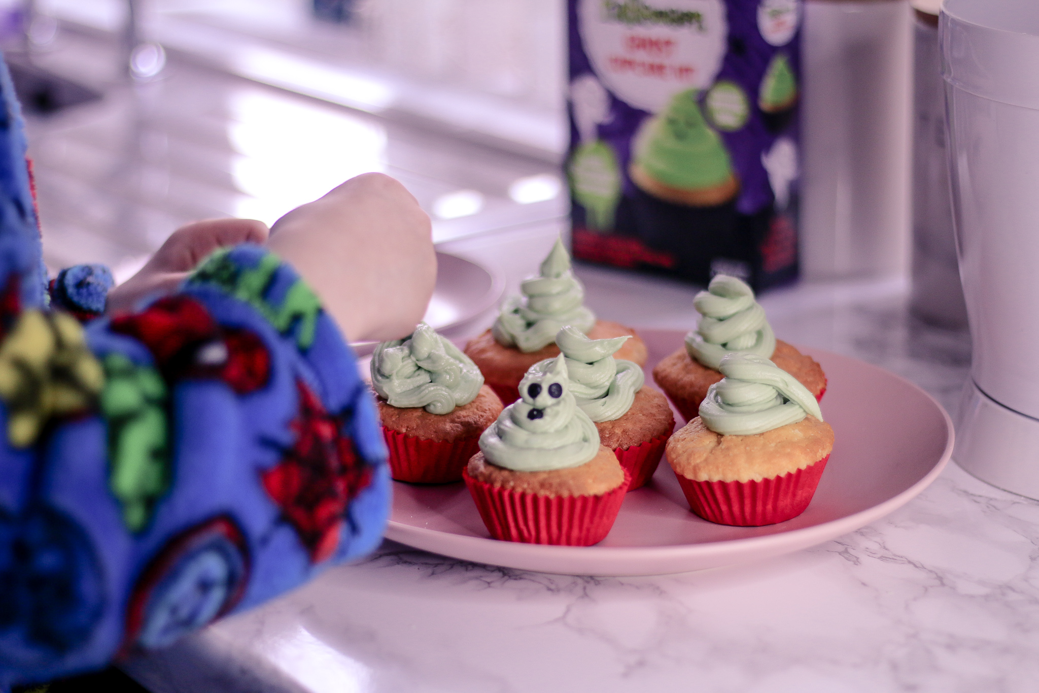 Close up photo of 6 cupcakes with green icing on a pink plate on top of a white marble kitchen worktop being decorated by a child