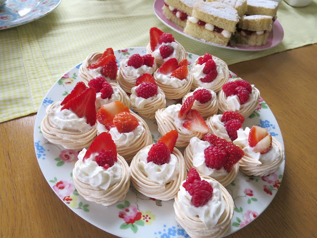 Home made birthday afternoon tea food and drink on Cath Kidston plates perfect for Spring mini pavlova with cream and berries