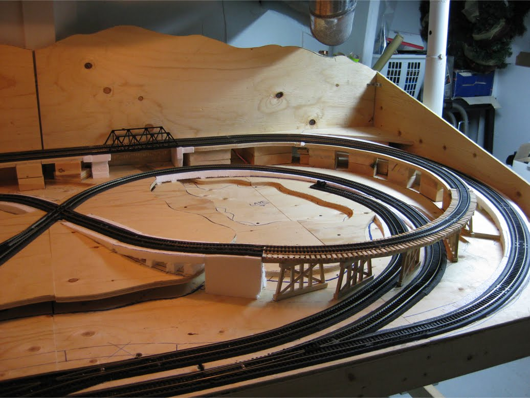 Model railroad benchwork with completed track on foam roadbed and unpainted wooden train trestle