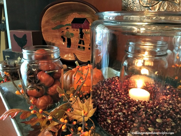 Close up of the glass jars filled with pumpkins and kernels decorated for Fall from Walking on Sunshine.