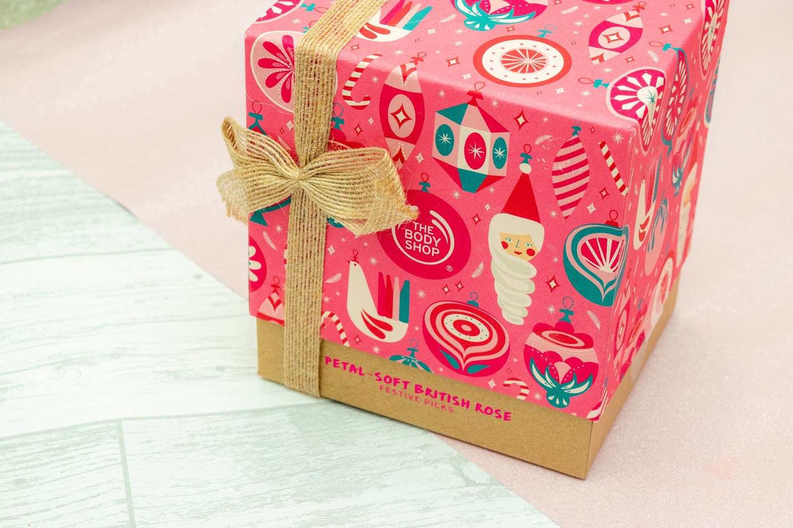 A pink box with Christmassy illustrations and a brown twine ribbon.