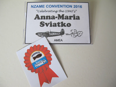 Name tag for NZAME convention 2016, with a tiny chocolate fish on a backing paper printed with a 'winner' rosette.