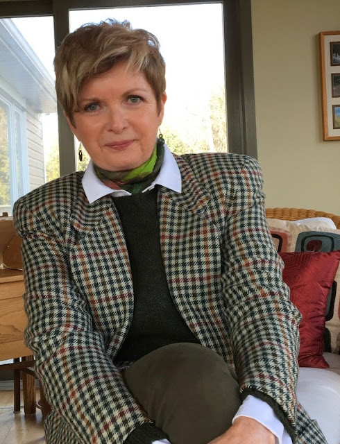 woman in checked jacket, green sweater and scarf, and white blouse