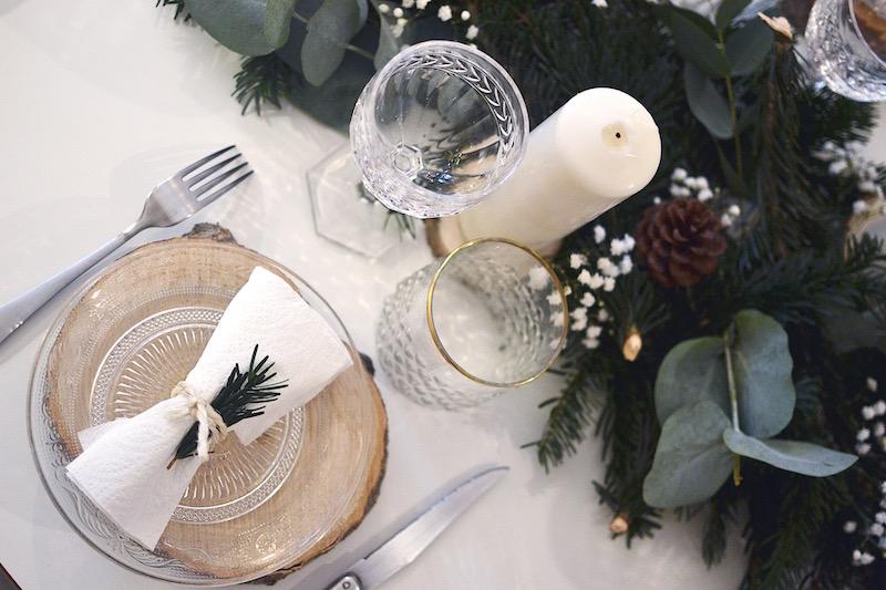 rondin de bois, assiette en verre maisons du monde, serviette blanche et branche de sapin
