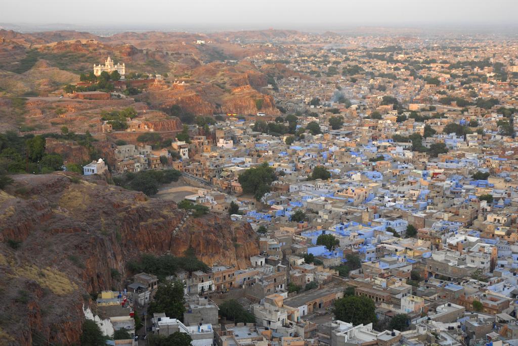 Det glorværdige Mehrangarh Fort ligger på en enorm stenet klippeformation, som dominerer den engang ukuelige blå by. I skumringen føler man næsten at være en del af en ægte film, mens det kamera-skyggende palads kigger over fantastiske stenmure, og hvor man kan fornemme og høre borgerne summe i det indfældede kaos nedenfor. Dette fotografi viser det blå landskab i byen Jodhpur i Rajasthan, Indien.