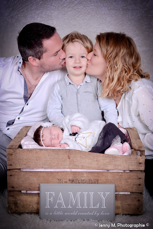 portrait de famille avec bébé bisou au grand frère de papa et maman