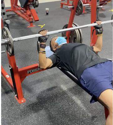 Black male lifting barbell, flat bench
