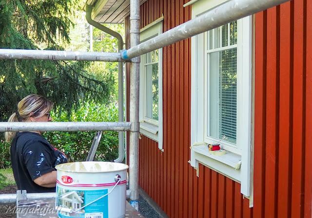 Punaisen puutalon julkisivun huoltomaalaus.